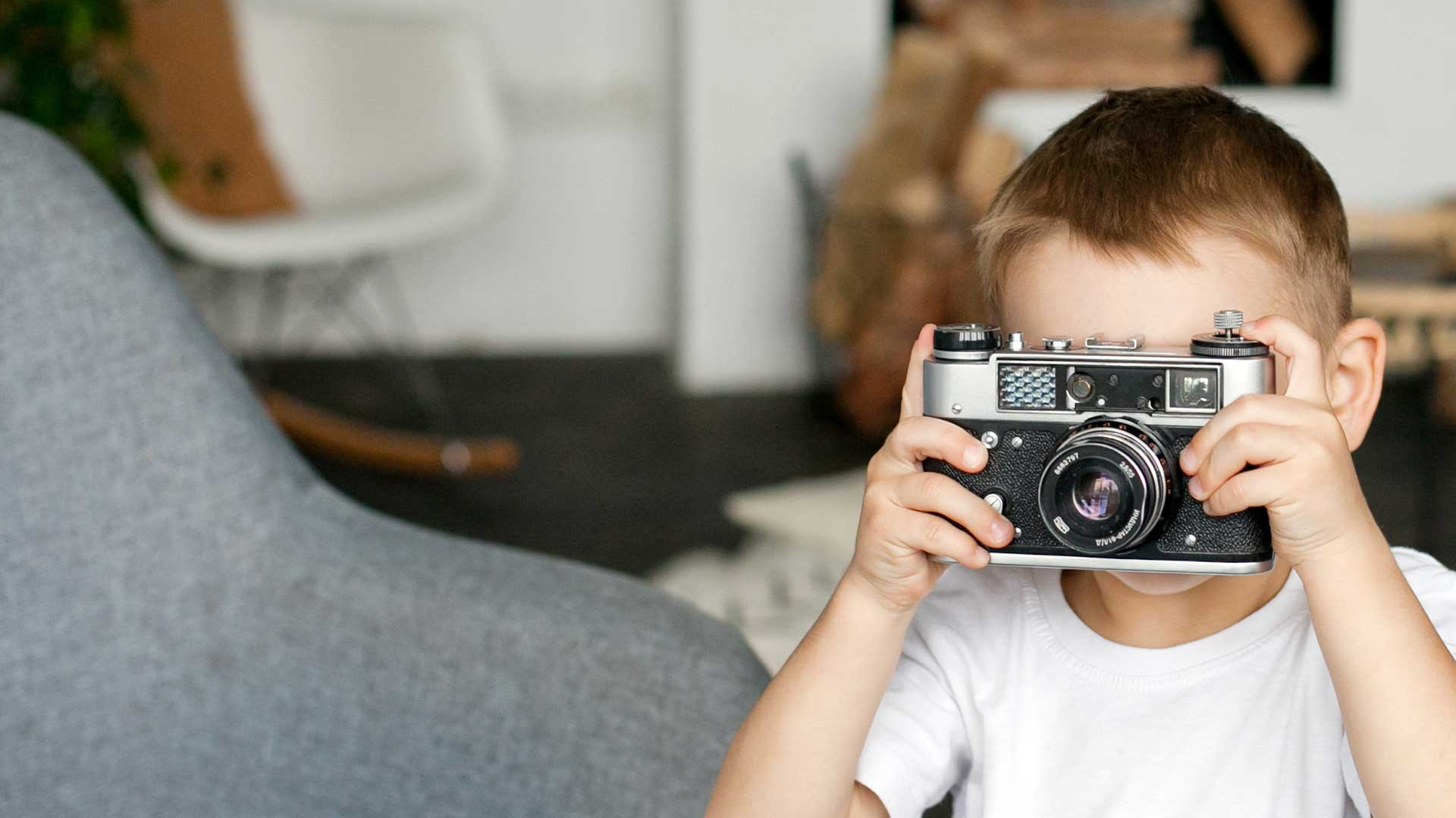 a-kid-playing-with-the-old-vintage-film-camera